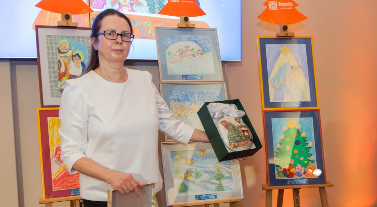 Organizatorka akcji Choinki Jedynki Dorota Truszczak prezentuje medalion, przekazany przez małżonkę prezydenta Agatę Kornhauser-Dudę