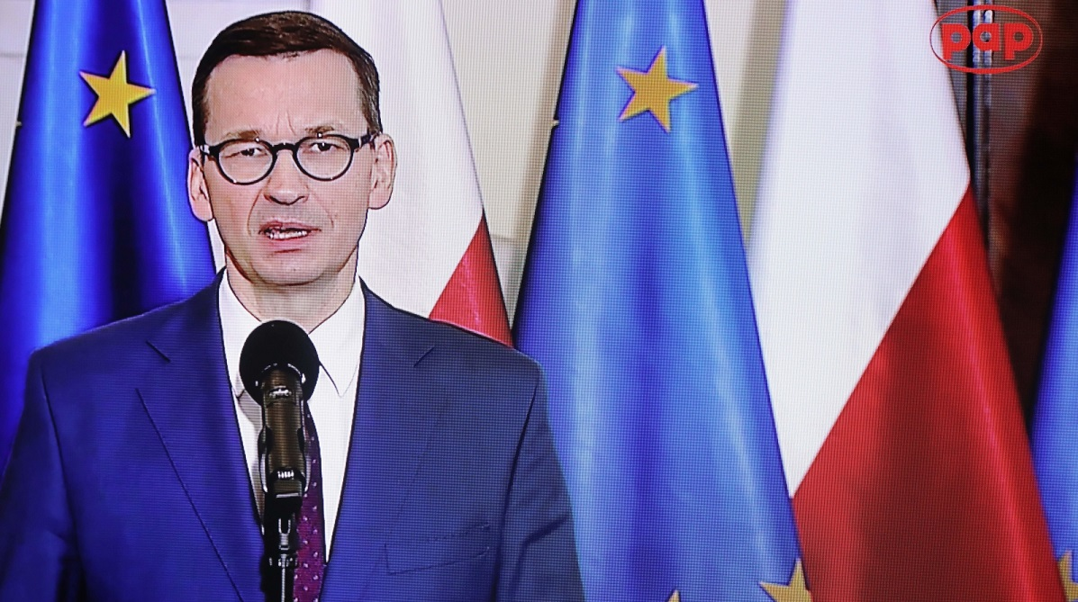 Polish PM Mateusz Morawiecki, seen on a screen, issues a statement on Wednesday on Poles in Belarus.