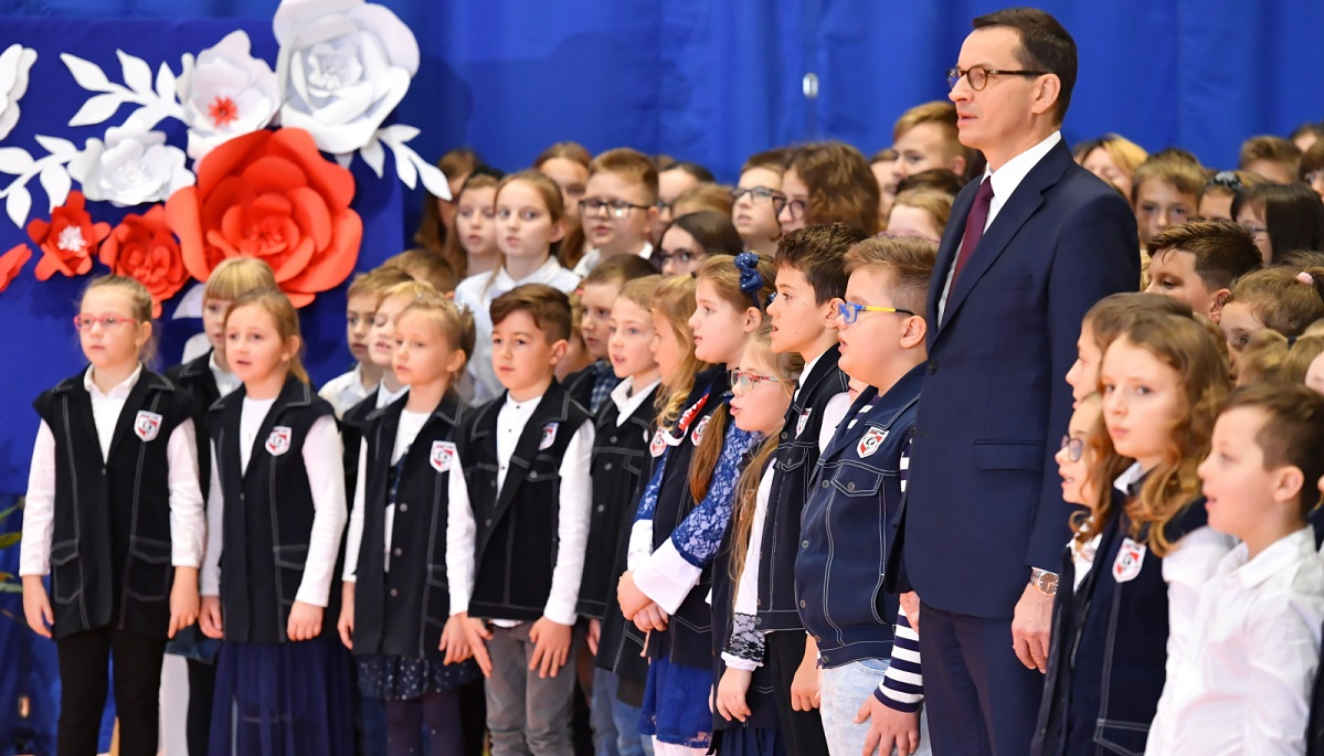 PM Mateusz Morawiecki (on the right) sings the national anthem alongside school pupils