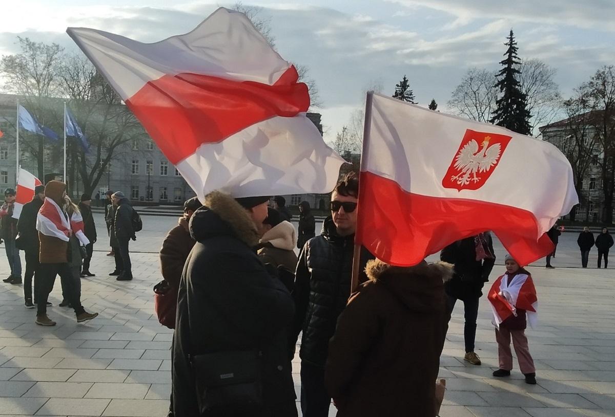 Вильнюс, 22 ноября 2019 г. Люди под белорусским и польским флагами на Кафедральной площади.