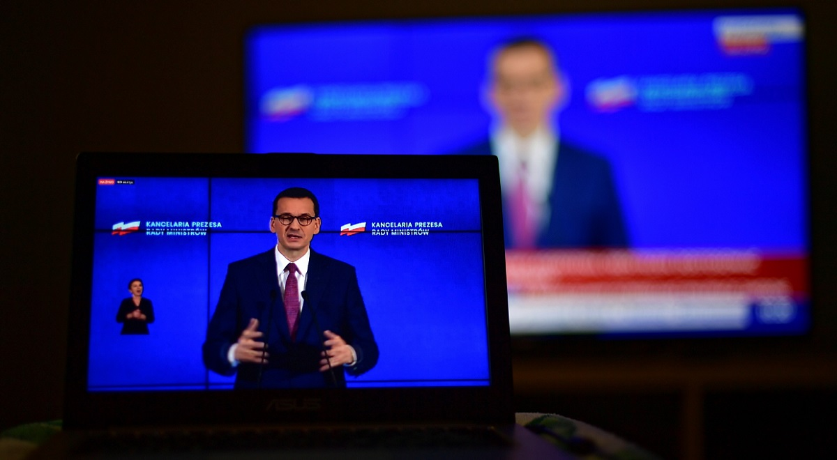 Polish Prime Minister Mateusz Morawiecki is seen on a television screen as he holds a news conference on Wednesday.