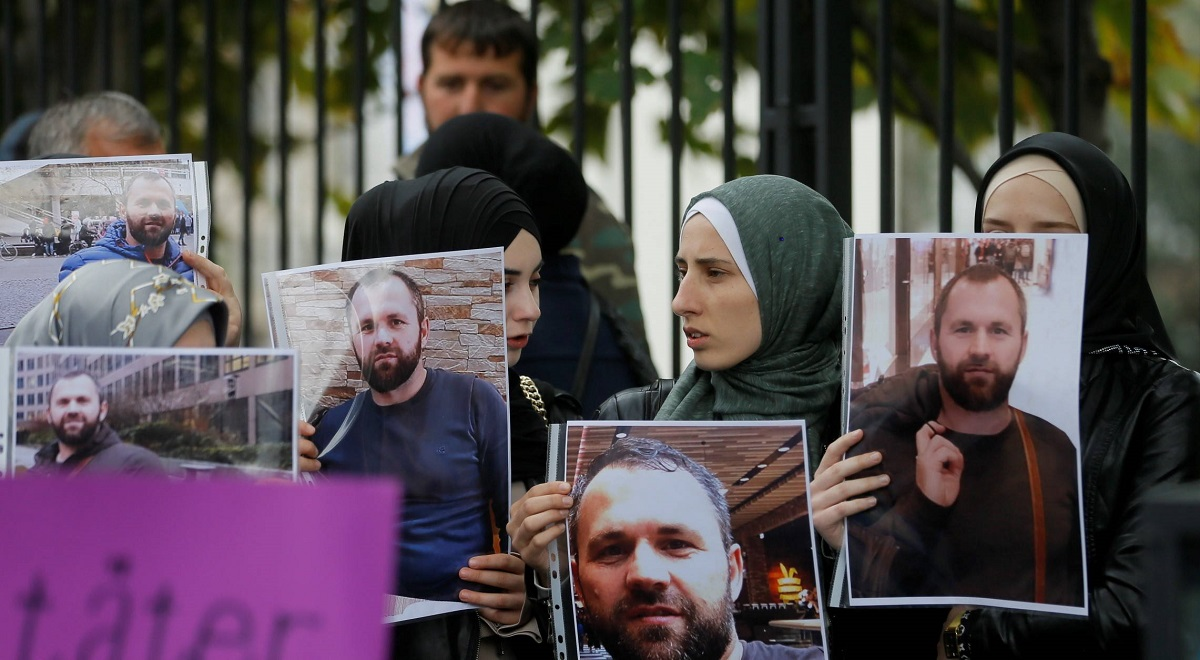People hold portraits of Zelimkhan Khangoshvili in front of the German embassy in Tbilisi, Georgia, 10 September 2019. Khangoshvili, a former militant activist, was shot dead in Berlin on 23 August.