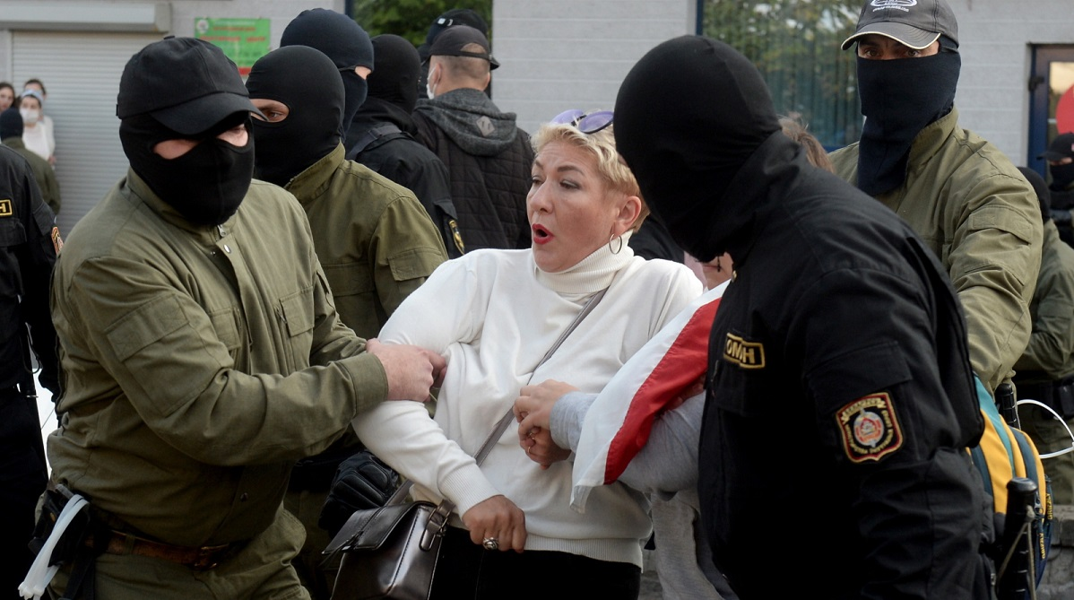 Belarusian policemen detain a participant of peaceful womens rally in Minsk on Saturday.