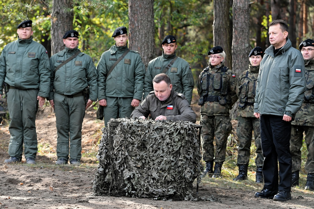 President Andrzej Duda signs into effect a plan to increase pay for Polands career soldiers during a visit to a military training site in Nowa Dęba in the southeast of the country.