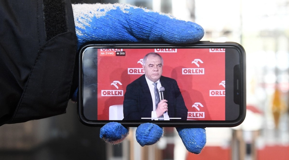Jacek Sasin, seen on a smartphone, during a televised press conference on Monday