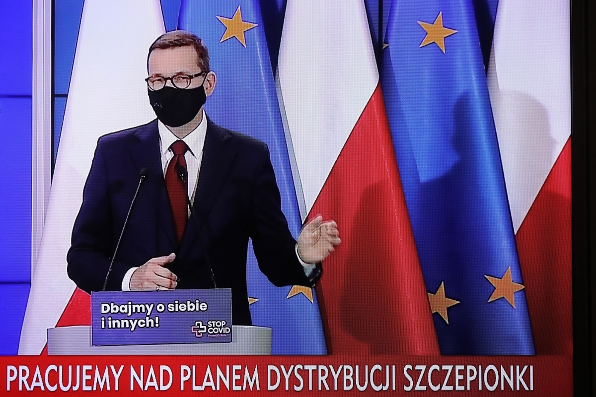 Polish Prime Minister Mateusz Morawiecki is seen on a television screen as he holds a virtual news conference on Monday, Nov. 9, 2020.