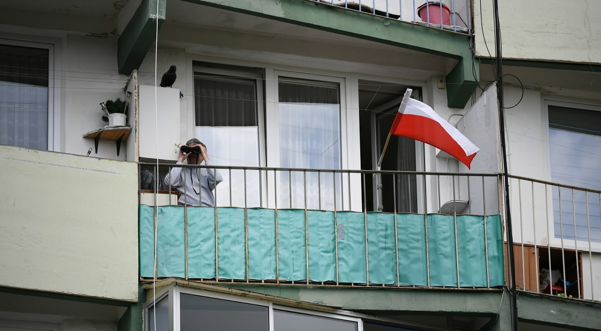 A man with binoculars watches a press conference by opposition presidential candidate Małgorzata Kidawa-Błońska in Gdańsk, northern Poland, 2 May 2020.