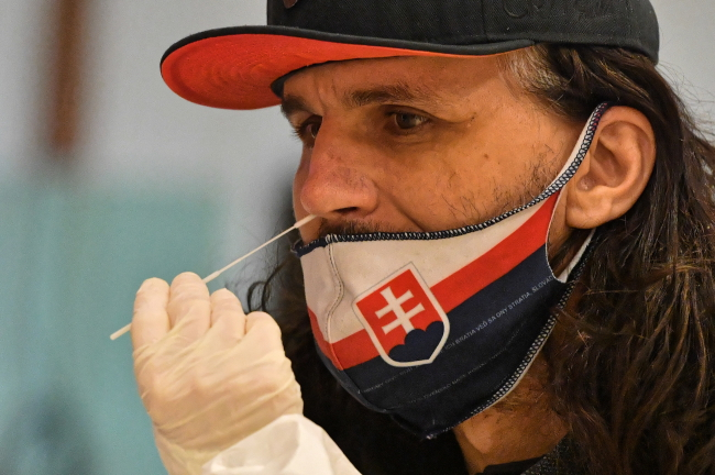 A nasal swab test for SARS-CoV-2, being performed  by Polish medics at an elementary school in Bratislava, Slovakia.