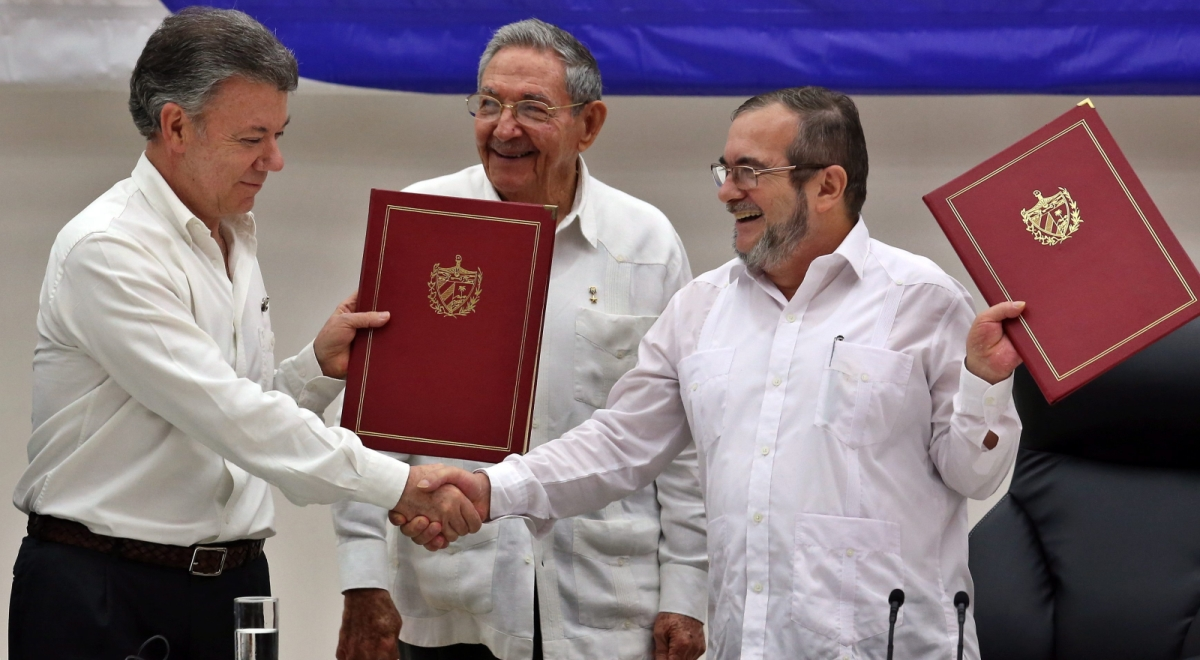 Prezydent Kolumbii Juan Manuel Santos,  prezydent Kuby Raul Castro i najwyższy dowódca partyzantki Rodrigo LondonoFARC delegate in Cuba, Londono Echeverri Timochenko (R) and Colombian President Juan Manuel Santos (L) shake hands before Cuban President Raul Castro (C) after signing the bilateral ceasefire agreement between the Colombian Governme