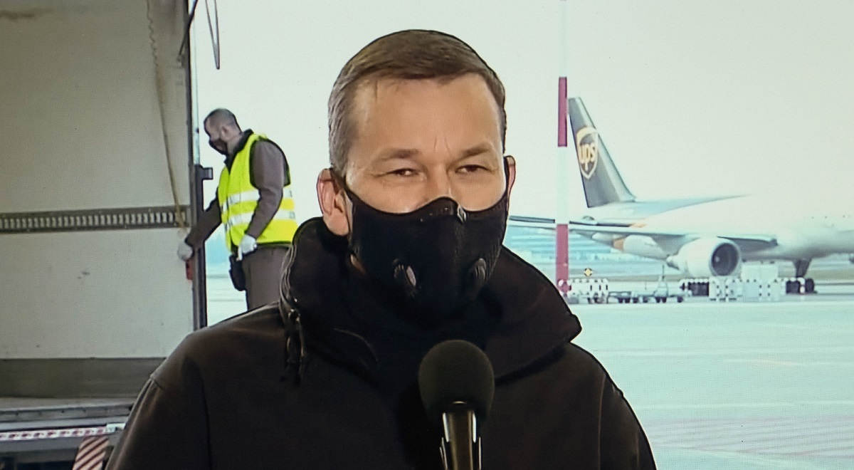 Polish Prime Minister Mateusz Morawiecki is seen on a television screen as he holds a news conference at Warsaw's Okęcie Airport on Monday mid-20c2800
