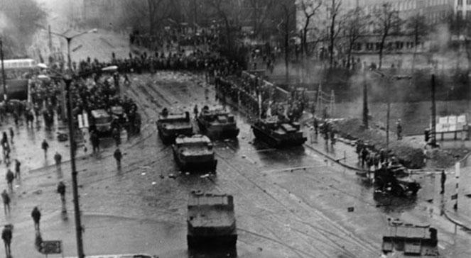 Kolumna wojskowych pojazdów i szpaler milicji blokujące skrzyżowanie ulic: Hucisko i 3 Maja, przy Komendzie Miejskiej Milicji Obywatelskiej. Gdańsk, 15.12.1970